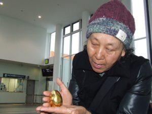 金の卵に触れる女性